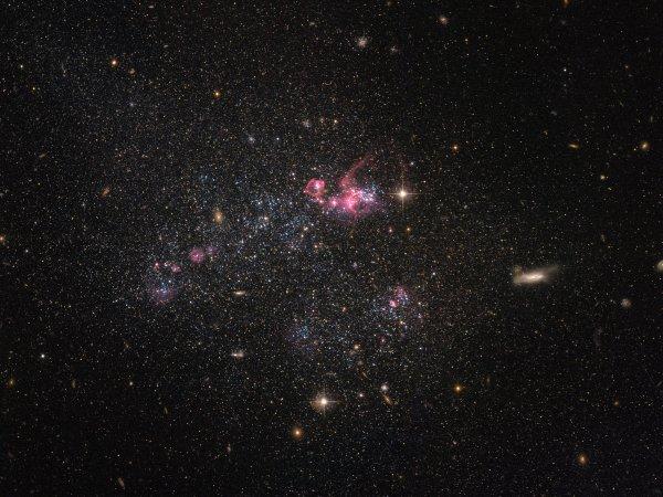 Ученые показали на фотоснимках Hubble развалившуюся карликовую галактику